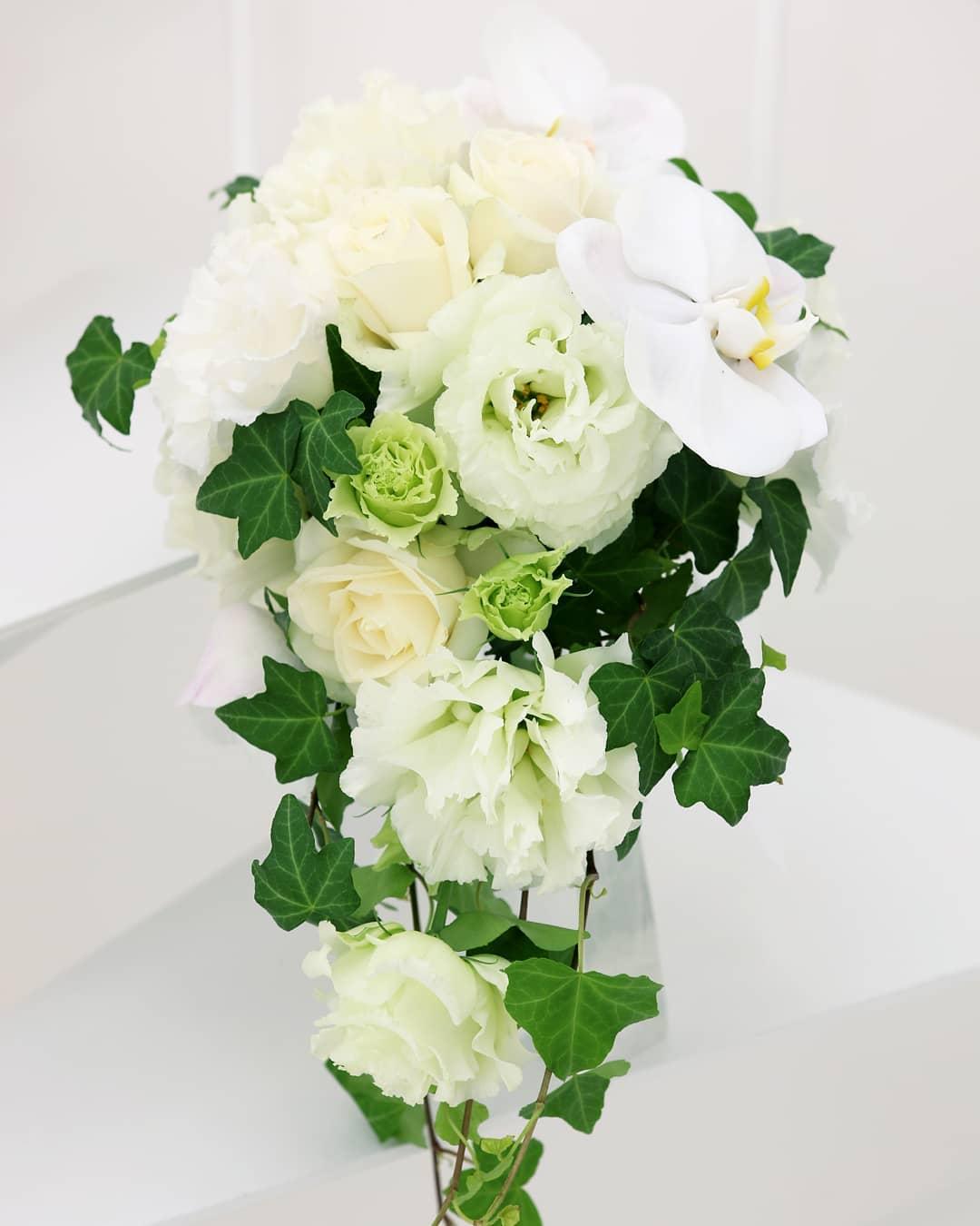 スタッフによる今月のお花。白薔薇、トルコ桔梗、胡蝶蘭、アイビーを使ったブライダルブーケ。